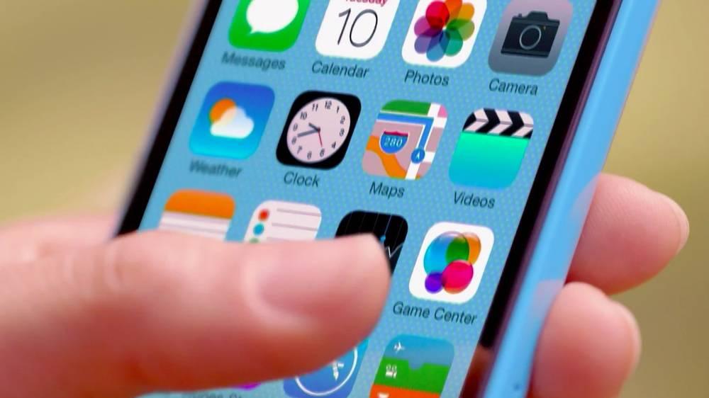 Hand holding iPhone 5C using iOS 7 - AmongTech